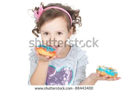 Picture of funny little girl eating colorful donuts on white background
