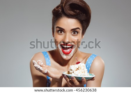 Picture of funny pin-up girl eating cake at studio