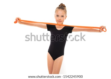 Picture of girl gymnast in black trico in full height keep a jumping-rope in her hands isolated on a white background
