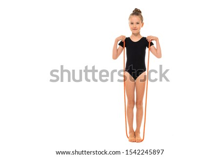 Picture of girl gymnast in black trico in full height stands on a jumping-rope isolated on a white background