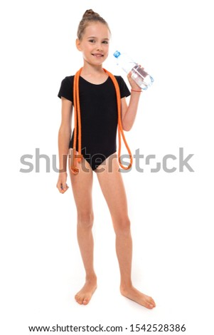 Picture of girl gymnast in black trico in full height with a jumping-rope around her neck and a bottle of water in hand isolated on a white background