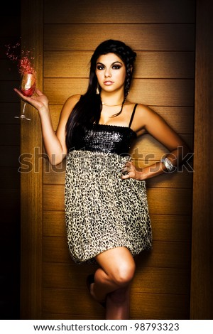 Picture Of Glamour And Poise With A Beautiful Young Woman Standing In Front Of Nightclub Wall Holding A Glass Of Unsettled Wine While Splashing Out On The Town