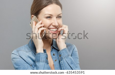 Picture of good-looking girl dressed in denim shirt turned right, isolated on gray background holding cellphone in right hand and talking with positive smile and laughing at news she is hearing. #635453591