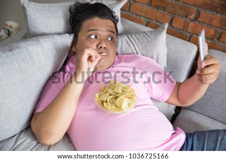 Picture of greedy person feels hungry and eat snack while leaning on the couch using smart phone #1036725166