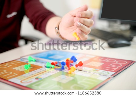 Picture of hand is throwing tokens on the ludo.