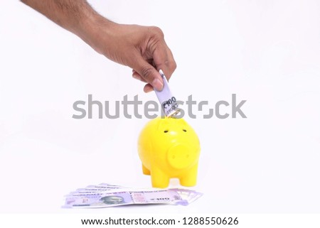 Picture of hand putting money in yellow piggy bank. on the white background.