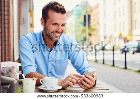 Picture of handsome man using smart phone at outdoors cafe #533600983