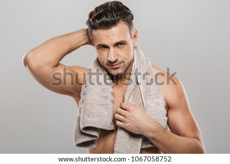 Picture of handsome mature man standing isolated over grey wall background naked. Looking camera holding towel.