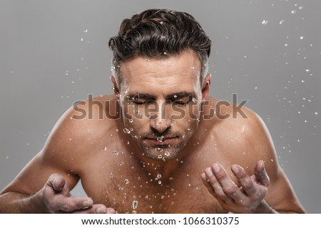 Picture of handsome mature man standing isolated over grey wall background naked washing his face.