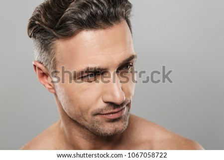 Picture of handsome serious mature man standing isolated over grey wall background naked. Looking aside.