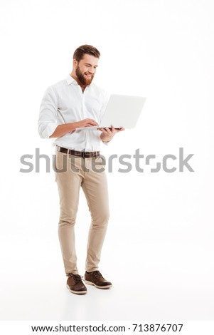 Picture of handsome young bearded man standing over white wall background isolated. Looking aside using laptop.