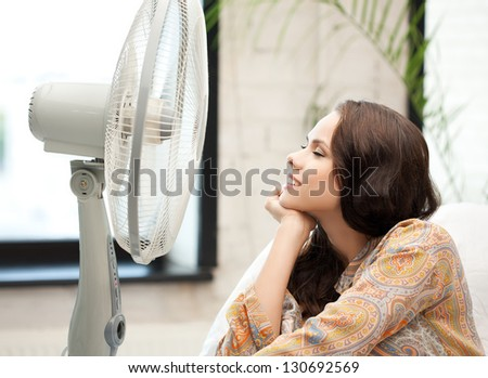 picture of happy and smiling woman sitting near ventilator - stock photo