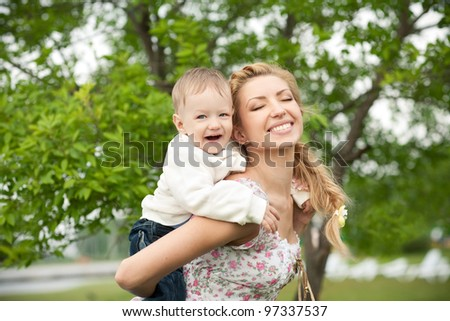 picture of happy baby with mother enjoying nature - stock photo