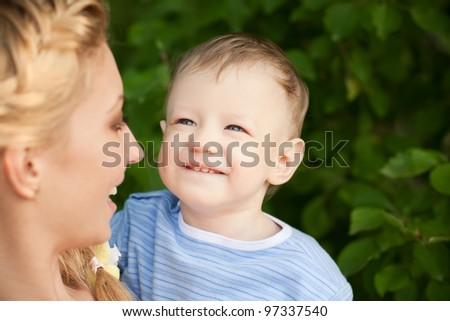 picture of happy baby with mother on a background of green leaves - stock photo