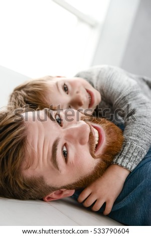 Picture of happy bearded father dressed in blue sweater playing with his little cute son in room indoors