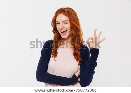 Picture of happy beautiful young redhead lady standing isolated over white wall background. Looking camera showing okay gesture.