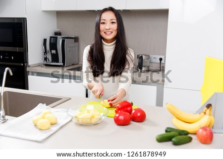 Picture of happy brunette cutting potatoes at table with vegetables and fruits