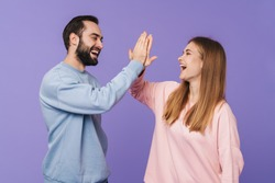 Picture of happy cheery optimistic loving couple posing isolated over purple background giving high five.