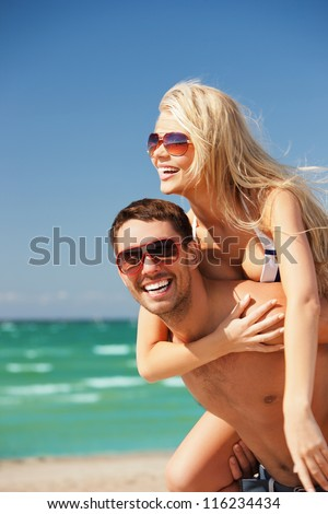 picture of happy couple in sunglasses on the beach (focus on man).