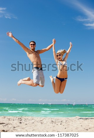 picture of happy couple jumping on the beach.