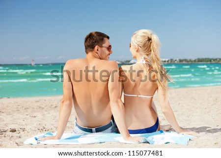 picture of happy couple sitting on the beach.