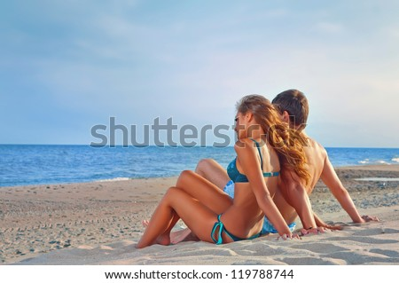picture of happy couple sitting on the beach