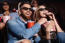 Picture of happy friends sitting in cinema watch film eating popcorn and drinking aerated sweet water.