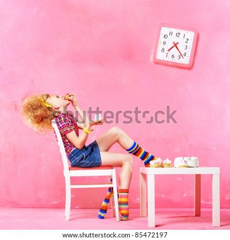 Picture of happy little girl eating cake isolated on pink interior