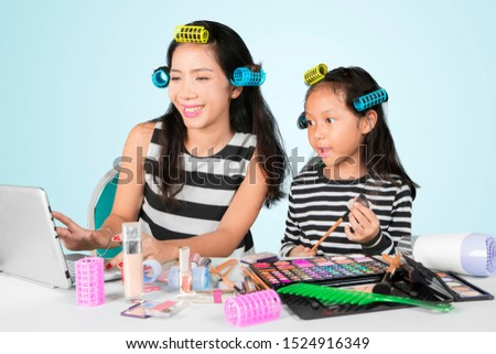 Picture of happy mother watching makeup tutorials on the laptop while doing makeup with her daughter in the studio