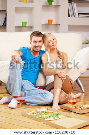 picture of happy romantic couple with remote - stock photo
