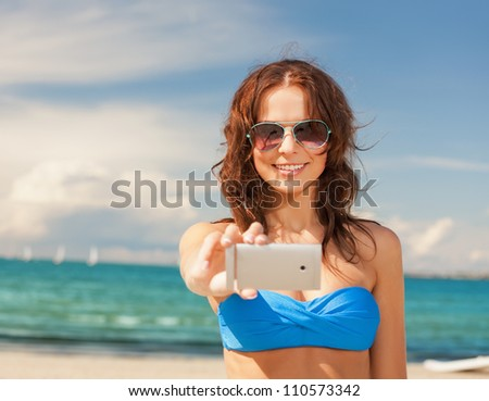 picture of happy woman with phone on the beach.