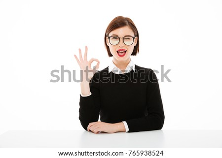 Picture of happy young business lady wearing glasses sitting at the table isolated over white background. Looking camera showing okay gesture.