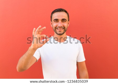Picture of happy young handsome man standing isolated over red wall background. Looking camera showing okay gesture.