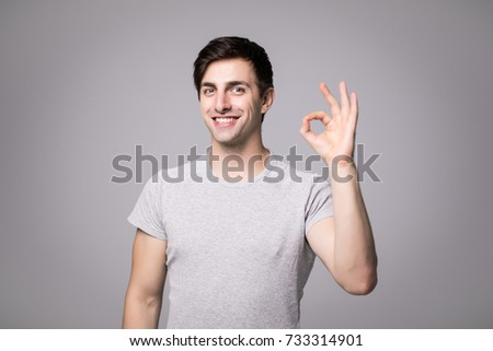 Picture of happy young man dressed in grey t-shirt isolated over grey wall background showing okay gesture.