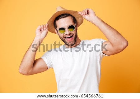 Picture of happy young man standing isolated over yellow background. Looking at camera.