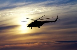 Picture of helicopter at sunset. Silhouette of helicopter on sunset sky.