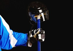 Picture of hockey helmet on hockey player stick