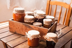 Picture of home made jam  in jars. Homemade preserves (conserve) concept in country kitchen. Rustic style.