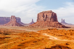 Picture of iconic Merrick Butte rock formation in Oljato-Monument Valley taken on a summer cloudy day from John Ford's point. The scenic drive dirt road with tourist cars winds through the red sand.