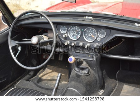 Picture of inside an unknown and old car with some damages due to the age.