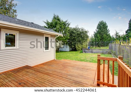 Picture of Large wooden back deck. House exterior. There is a small shed in the background of green backyard garden. #452244061