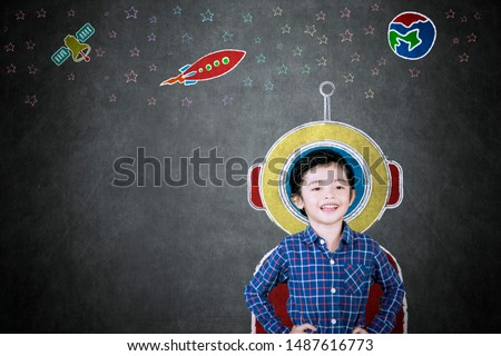 Picture of little boy smiling at the camera while imagining being an astronaut