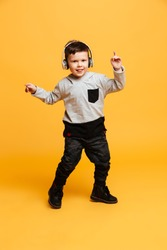 Picture of little funny boy child standing isolated over yellow background. Looking camera listening music with headphones.