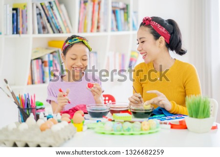 Picture of little girl dyeing eggs for Easter with her mother in the library