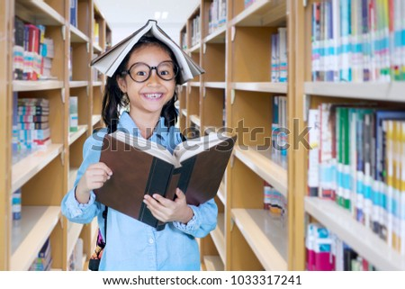 Picture of little girl looking at the camera with a book over her head while standing in the library