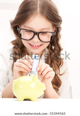 picture of little girl with piggy bank and money - stock photo
