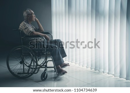 Picture of lonely elderly man looks pensive in the retirement home while sitting in the wheelchair