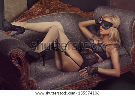 picture of lovely blonde in lingerie with sleep mask on her eyes lying on the sofa