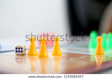 Picture of ludo tokens and dice.