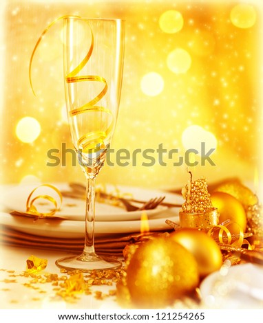 Picture of luxury festive table setting, closeup image of beautiful white utensil decorated with golden shiny balls and candle on blur glowing background, New Year eve, Christmas holiday dinner party